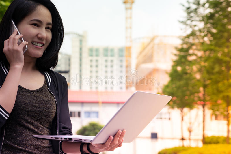 A woman is on call and holding laptop computer stock photography