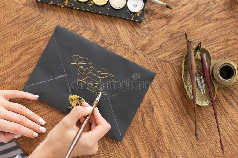 Woman calligrapher is holding a pen with ink and signs a letter in handwritten font. Close-up. Soft focus. Top view. stock photo
