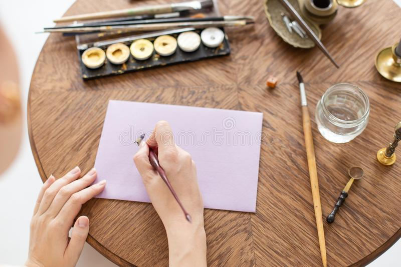 Woman calligrapher is holding a pen with ink and signs a letter in handwritten font. Close-up. Soft focus. Top view. stock photography