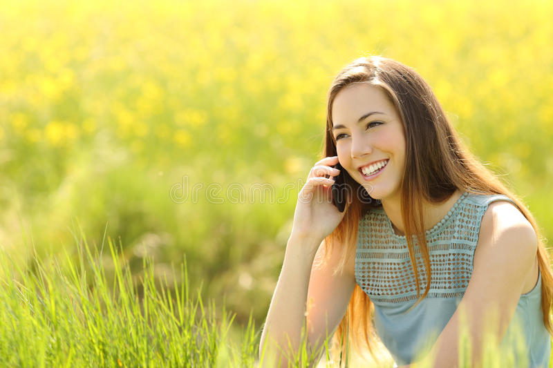 Woman calling on the mobile phone in a green field stock images