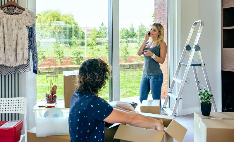 Woman calling on the phone while make a move. Woman calling on the phone while she and her husband make a move stock photos