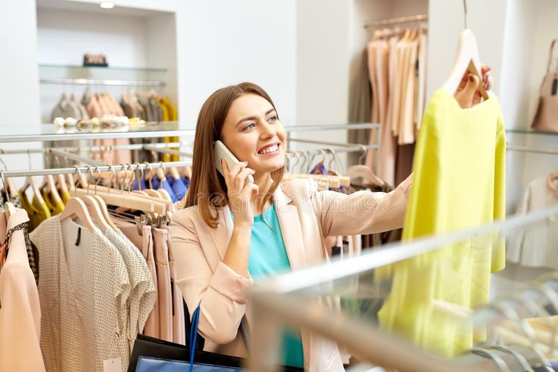 Woman calling on smartphone at clothing store. Shopping, fashion, sale and people concept - happy young woman choosing dress and calling on smartphone in mall or stock photo