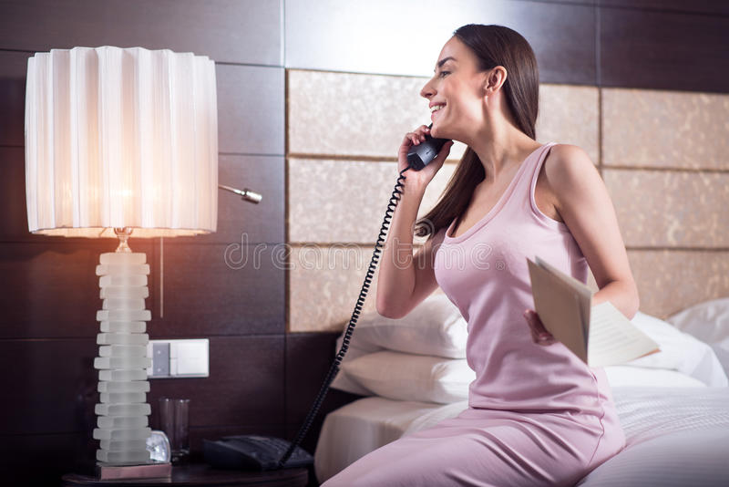 Woman calling to service in hotel. Lest ask them. Beautiful excited young woman sitting on the bed in the hotel and calling to the service royalty free stock image