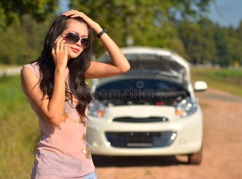 A woman calls for assistance. After her car broke down royalty free stock image