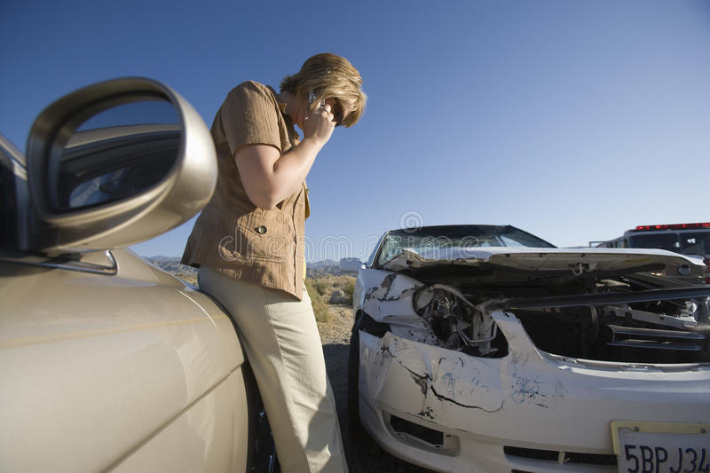 Woman Calls For Assistance Using Her Mobile Phone. Side view of a women calls for assistance using her mobile phone, after her car met with an accident royalty free stock images