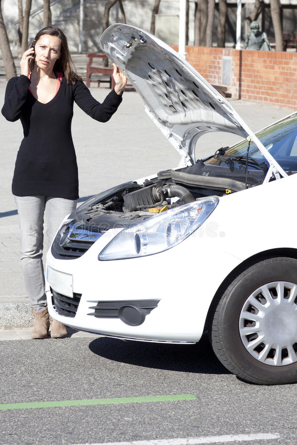 Woman calls after car is broken. Woman calls roadside assistance after car brakes stock images