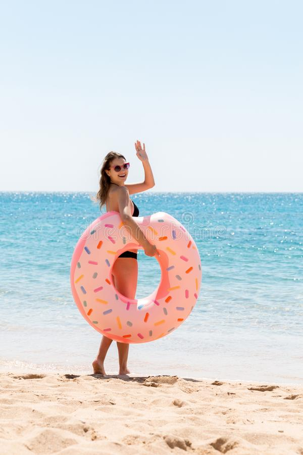 Woman calls to swim in the sea and waves her hand. Girl relaxing with donut on the beach and playing with inflatable ring. Summer stock images