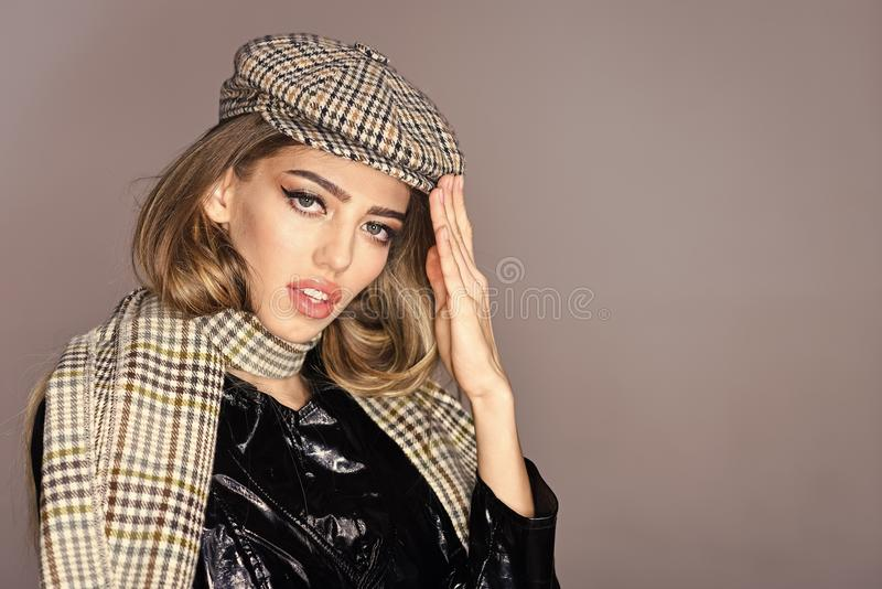 Woman on calm face in cloak with accessories. Girl with long hair wears plaid kepi, scarf, grey background, copy space royalty free stock photography
