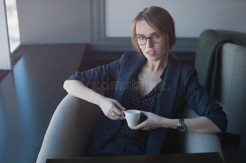 Woman came to the meeting. The bussineswoman in the cafe leaned back in his chair. In the hands holding a Cup of coffee. Looking at the camera royalty free stock photos