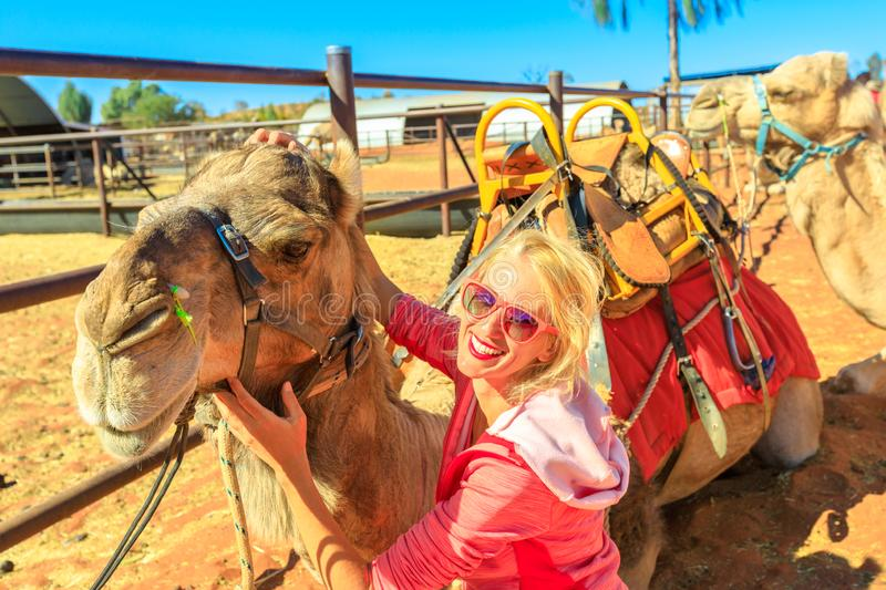 Woman with camel. Happy woman touches and interacts with camel. Australian desert of Northern Territory after a camel ride on red dunes of Red Center in Central royalty free stock images
