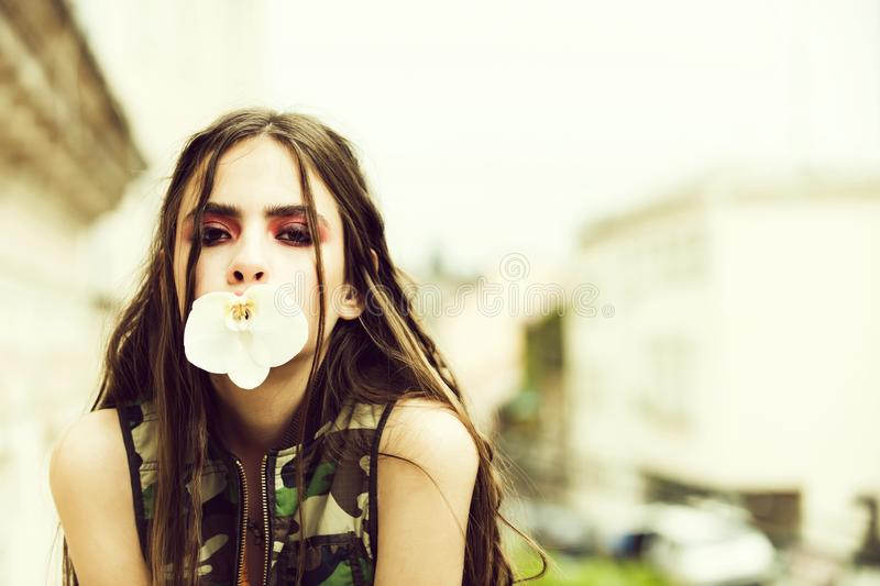 Woman in camouflage vest holding orchid flower in mouth royalty free stock image