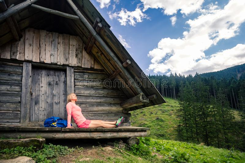 Woman camping and looking at inspiring mountain landscape. Young woman hiker camping and looking at beautiful view in Tatra mountains on hiking trip stock photo