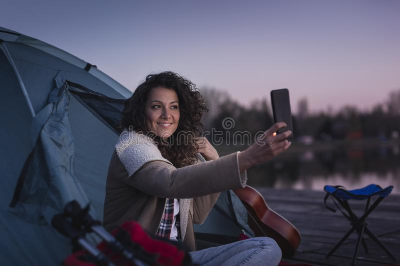 Woman camping and taking selfies stock photos