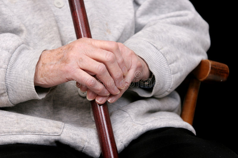 Woman and cane. One elderly woman's hands holding her cane in her lap royalty free stock photography