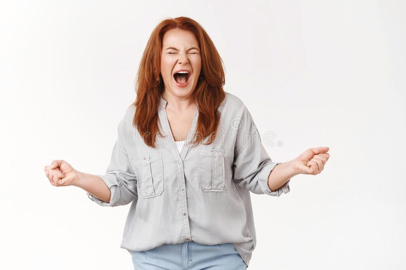 Woman cannot stand pressure release stress shouting fed up. Distressed annoyed redhead middle-aged mother clench fists royalty free stock photos