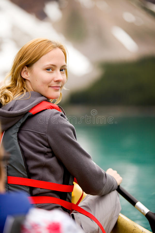 Woman in Canoe. A portrait of a smiling woman in a canoe on a glacial lake stock photos