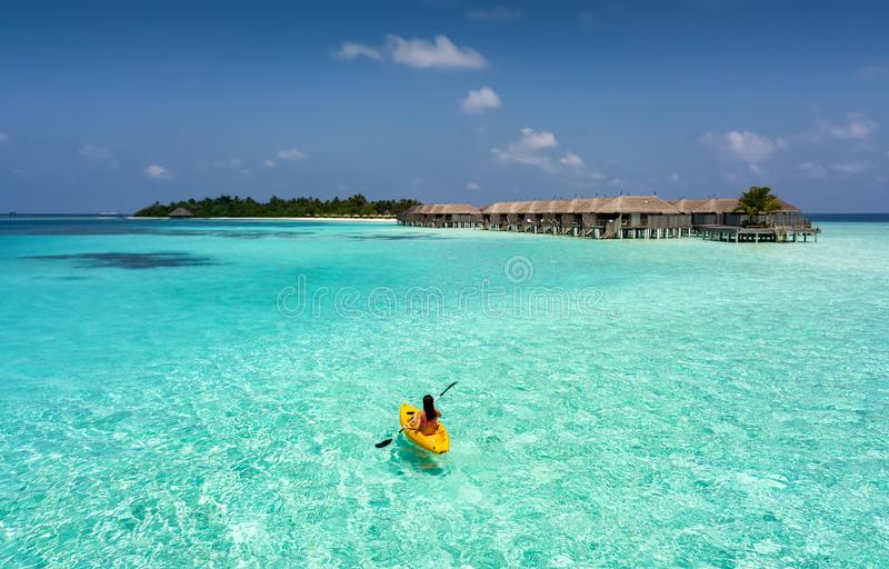 Woman in a canoe in the Maldives. Woman in a canoe over tropical, turqoise waters in the Maldives stock photos