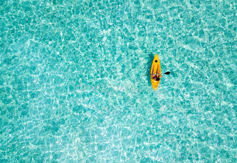 Woman in a canoe over turquoise, tropical waters stock photo