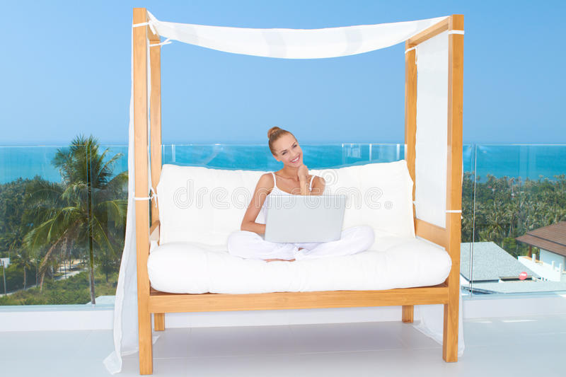 Woman on canopied seat with laptop stock image