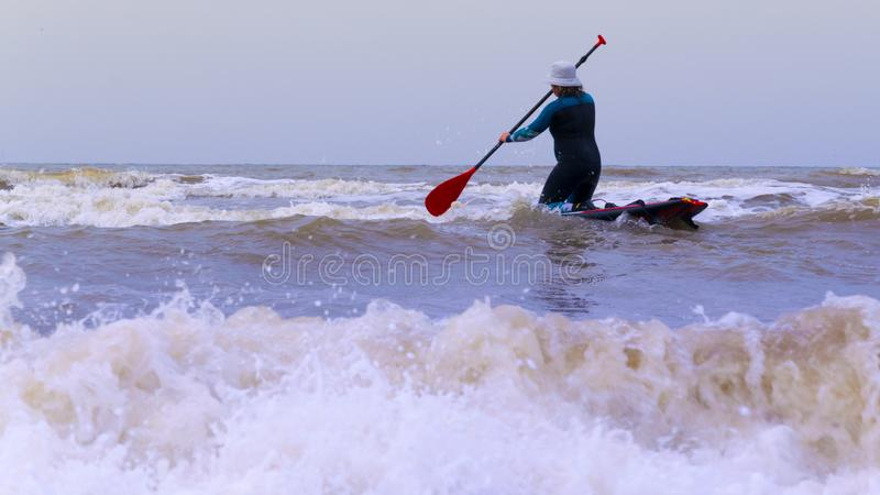 A woman with a cap on the head, practicing stand up paddle, on the North Sea in the Netherlands with large waves and strong winds royalty free stock photography