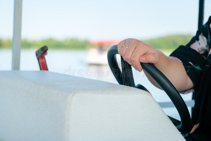 Woman captain holding the steering wheel in a boat. Summer time vacation with sailboat in an open waters, female captain in a royalty free stock photos