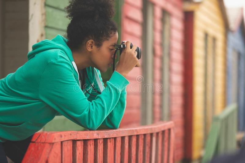 Woman capturing photograph while standing at beach hut. Side view of beautiful Mixed-race woman capturing photograph while standing at beach hut royalty free stock photography