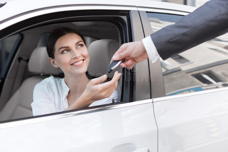 Woman at car dealership, buying new auto stock image