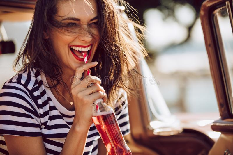 Woman in car enjoying drinking cola royalty free stock images