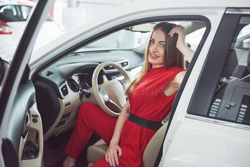 Woman in car indoor keeps wheel turning around smiling looking at passengers in back seat idea taxi driver against. Sunset rays Light shine sky Concept of exam royalty free stock images