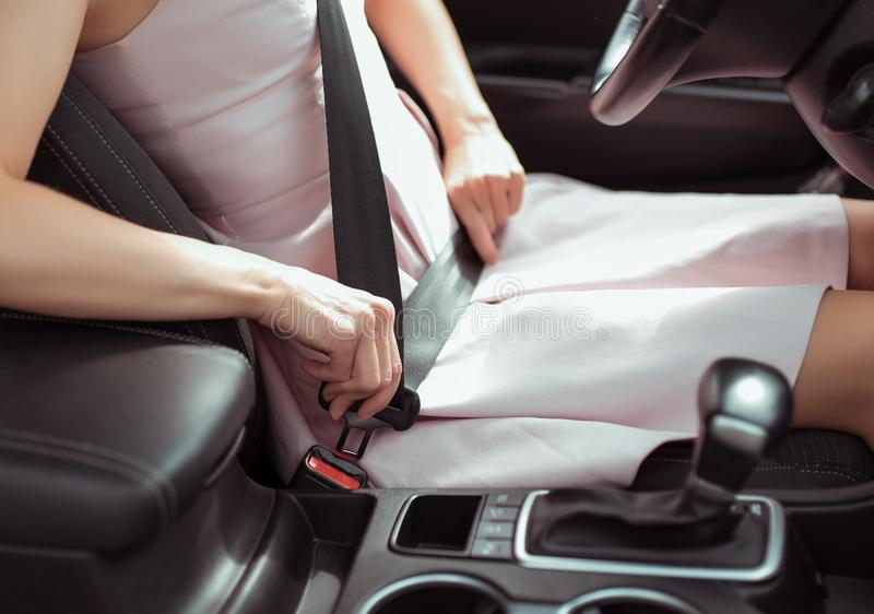 A woman in car interior, fastens her seat belt, pink dress, automatic gearbox, close-up, safety concept, detaches royalty free stock image