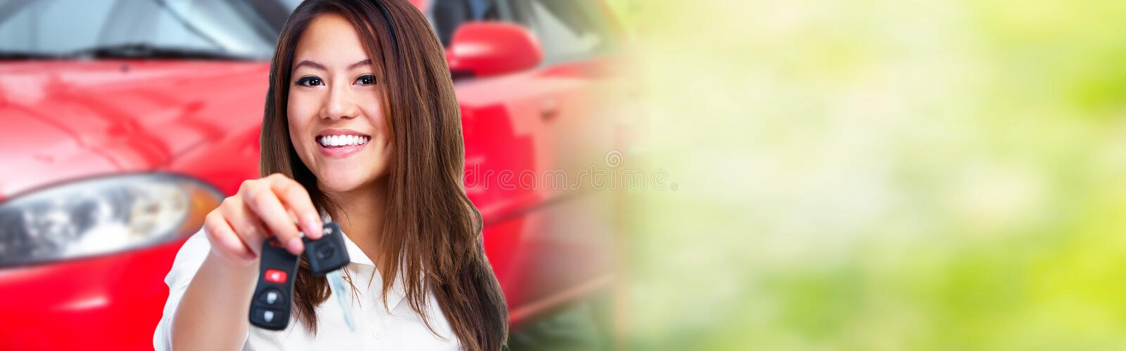 Woman with a car key. Auto dealership and rental concept background stock image