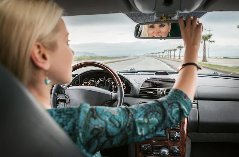 Woman in car look in rear view mirror stock photo