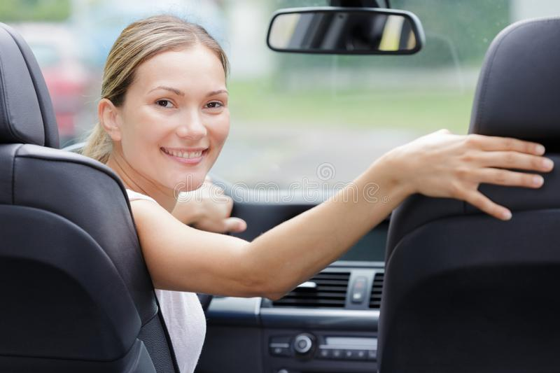 Woman in car looking back royalty free stock photography