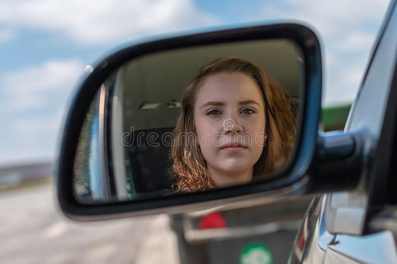 A woman in a car is looking into the rearview mirror stock photos