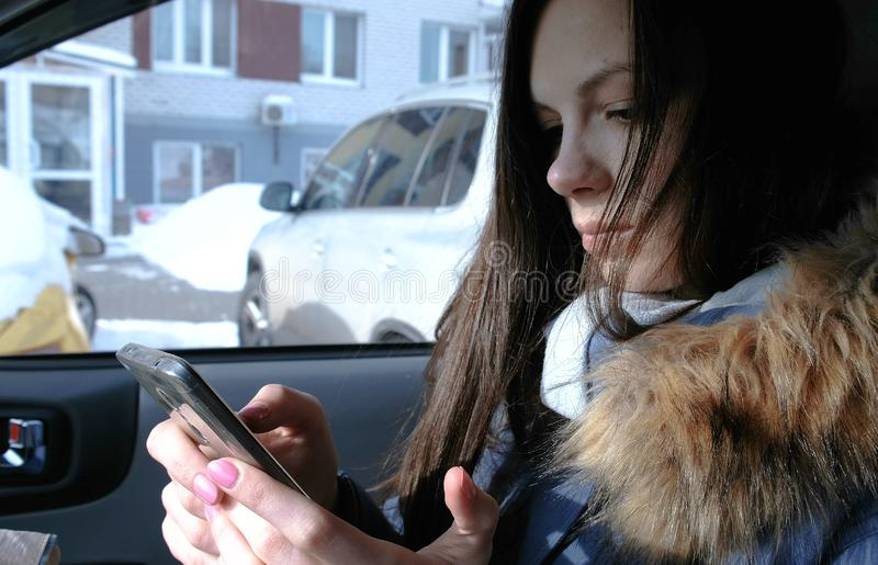 Woman in a car with a mobile phone. Young beautiful brunette woman looking something in the mobile phone. stock photography