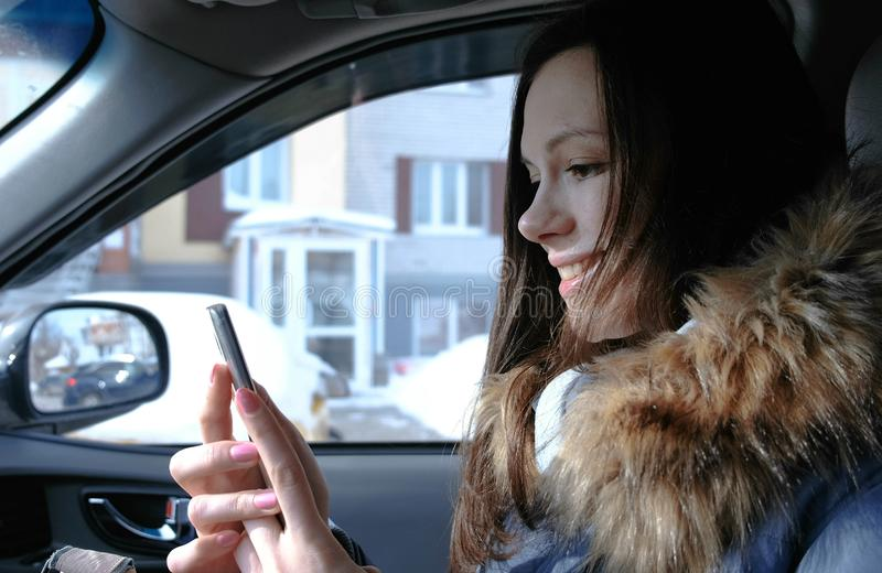 Woman in a car with a mobile phone. Young beautiful brunette woman looking something in the mobile phone. Woman in a car with a mobile phone. Young beautiful royalty free stock photos