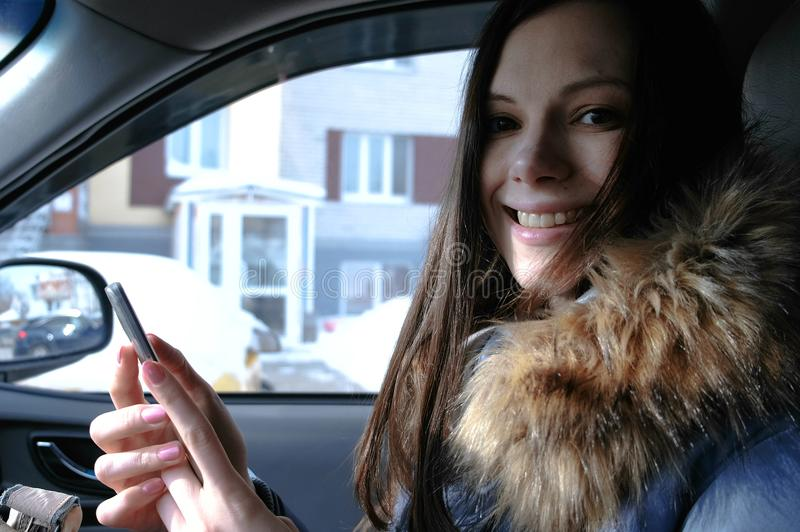 Woman in a car with a mobile phone. Young beautiful brunette woman looking at camera. stock photos