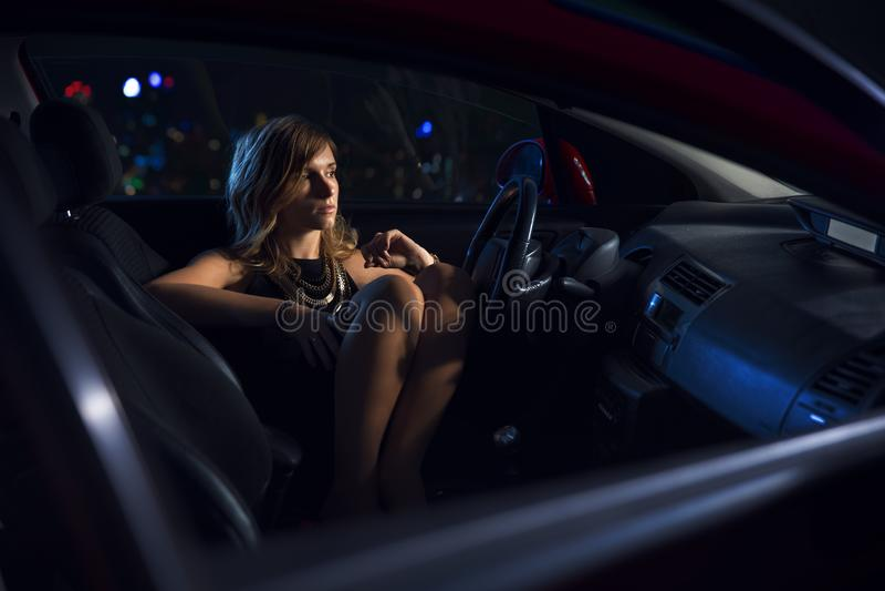 Woman in car night light stock photo