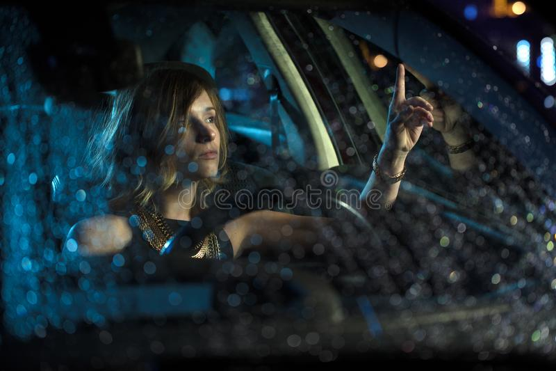 Woman in car night light stock photography