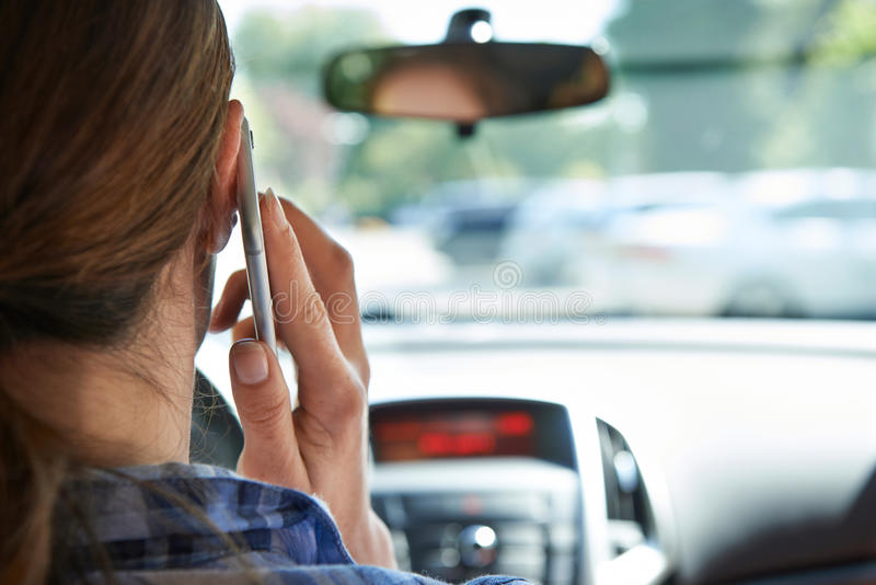 Woman In Car Talking On Mobile Phone Whilst Driving royalty free stock photo