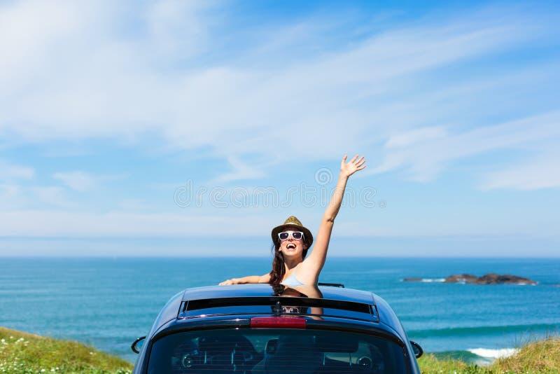 Woman on car vacation travel waving. Joyful woman waving on summer car travel vacation to the coast. Brunette girl having fun leaning out vehicle sunroof towards royalty free stock photo