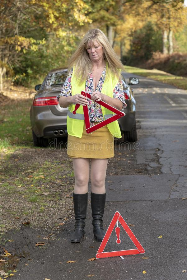 Woman with car and wearing a safety reflective jacket t and safety triangle royalty free stock photo