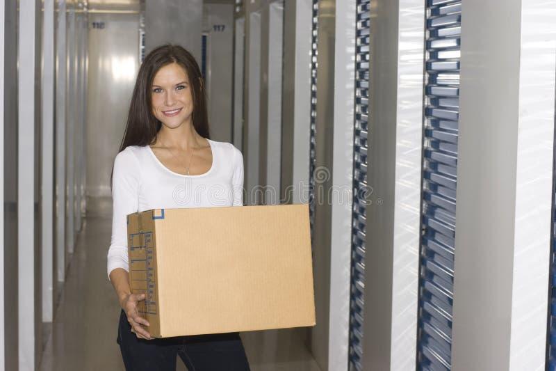 Woman with cardboard box storage locker royalty free stock photography