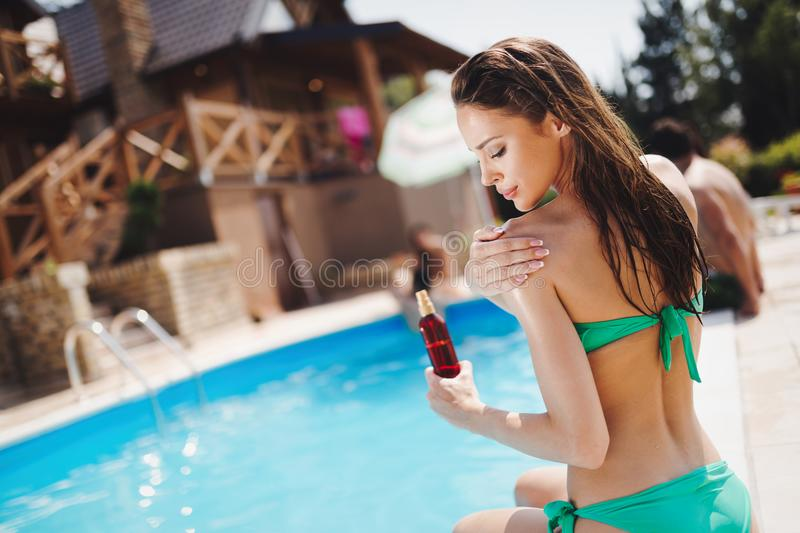 Woman careful not to get sunburn. By applying cream royalty free stock photo