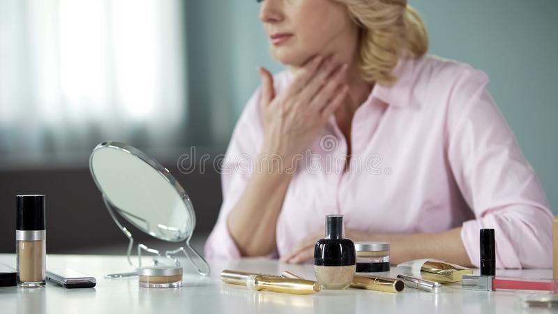 Woman carefully examining her aging and sagging skin pondering about lifting. Stock photo royalty free stock photos