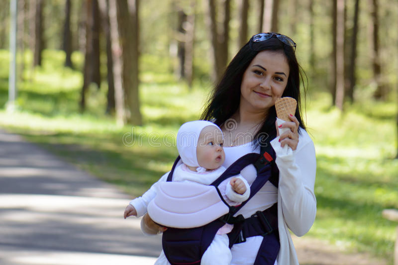 Woman caring child in baby carrier stock photo