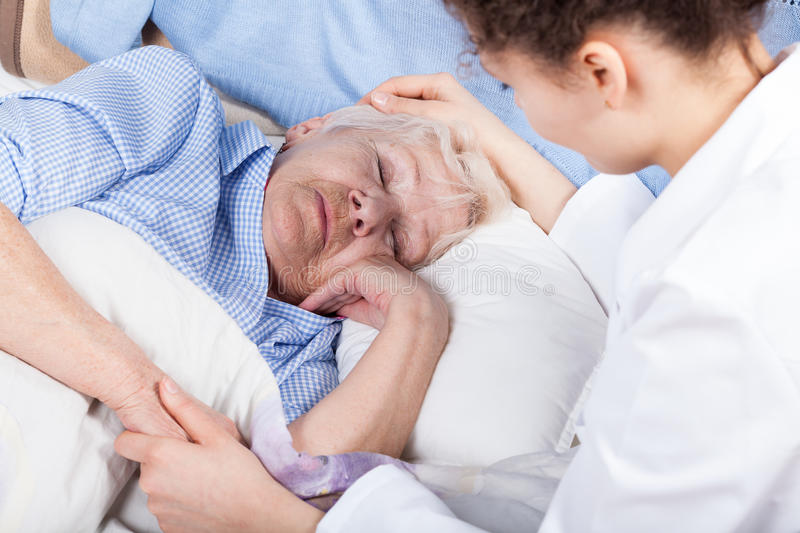 Woman caring about elderly lady stock images