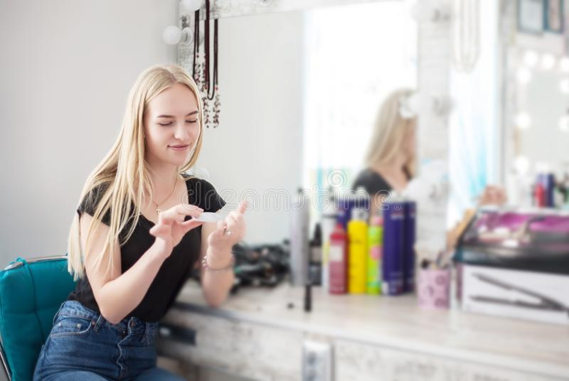 A woman is caring for her nails while sitting near a mirror royalty free stock photo