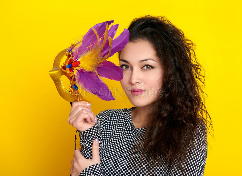 Woman in carnival mask with feather, beautiful girl portrait on yellow color background, long curly hair stock images
