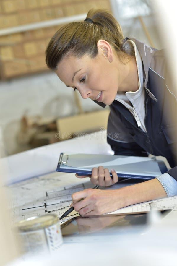 Woman carpenter designing plans royalty free stock photos